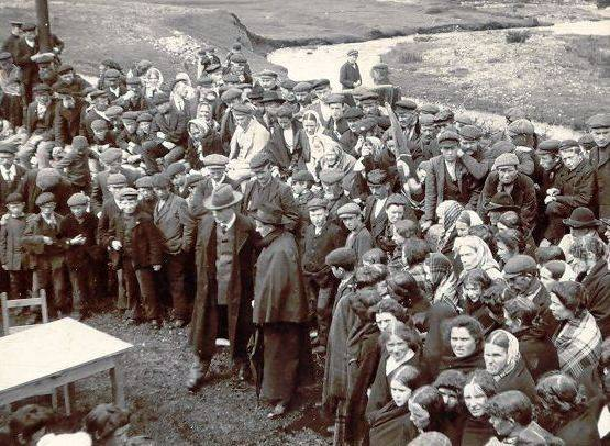 A Gaelic League aeraiocht (an outdoor festival of music, dance, and recitation) in Rosmuc, Co. Galway, c.1905. Pearse is standing to the front wearing a grey hat and a long black overcoat. OPW.